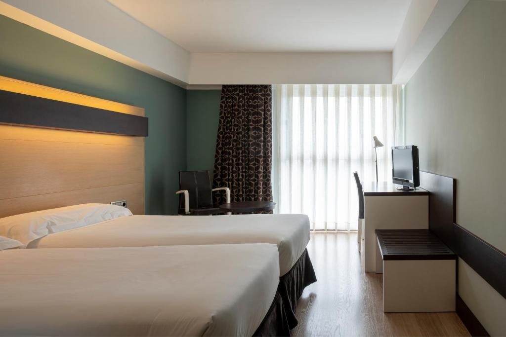 洛格罗尼奧城市酒店客房内的一张或多张床位