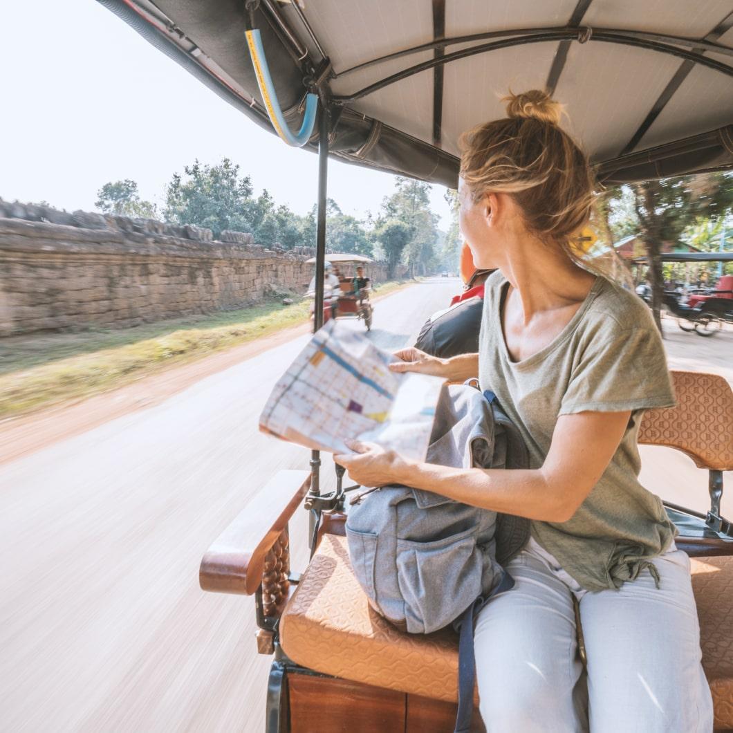 一名手持地图的旅行者坐在人力车后面
