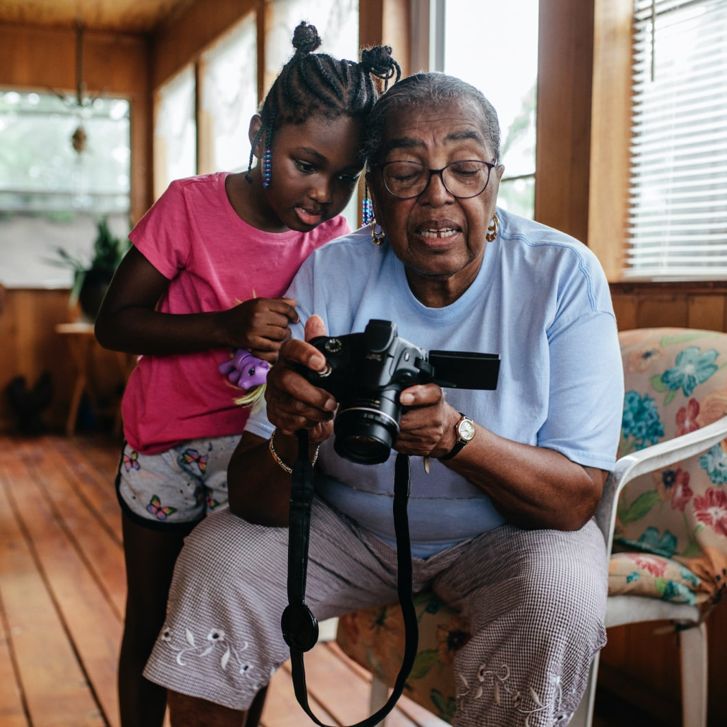 一名女孩和她的祖母正在看数码相机上的照片